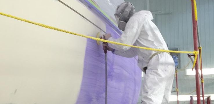 Worker preparing a boat hull for paint