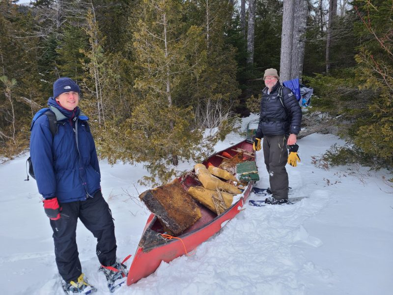 Chris Richmond and his son Carlton with an old canoe on snow